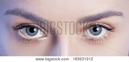 The eyes of beautiful woman face portrait close up on blue background