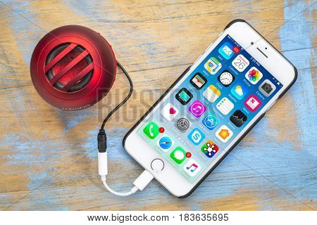 FORT COLLINS, CO, USA - APRIL 26, 2017: iPhone 7 smart phone by Apple Computer Inc with a small portable Rokono speaker plugged in..