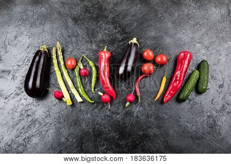 Different Fresh Seasonal Vegetables In Row On Black Table Top Background