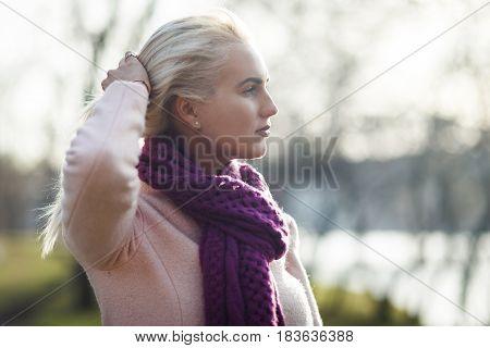 Blonde straightens hair in park at spring afternoon