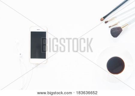 Smartphone with beauty make up brush set and coffee cup on white background Flat lay