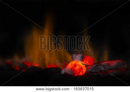 Red hot coal nugget in focus on dark background with flames. Background of raw coals with soft focus exclusion with color and temperature.