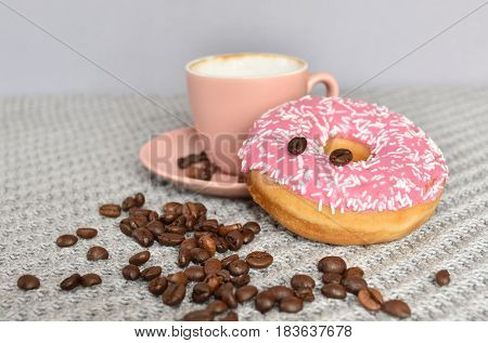 Colorful pink doughnut with coffeebeans and a espresso cup behind. Tasty foodphotography.