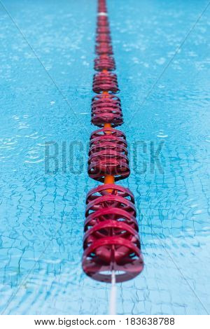 Swimming bath with red floats and clear blue water