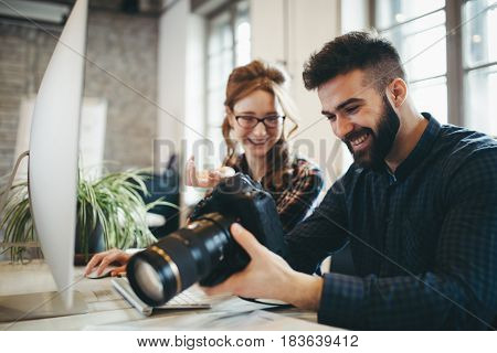 Company photo editor and photographer working together in office