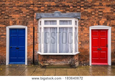 Blue and red doors with brick wall at England, UK.