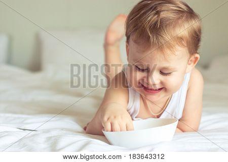 Little Cute Boy Having Breakfast In Bed. Boy Playing In Bed. Breakfast In Bed.