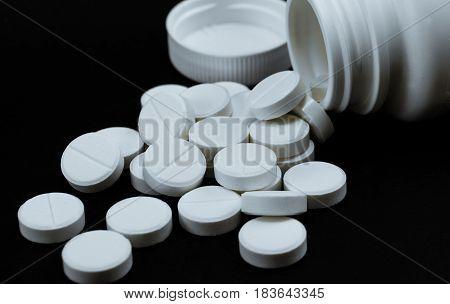 White drug tablet pills isolated on black background.