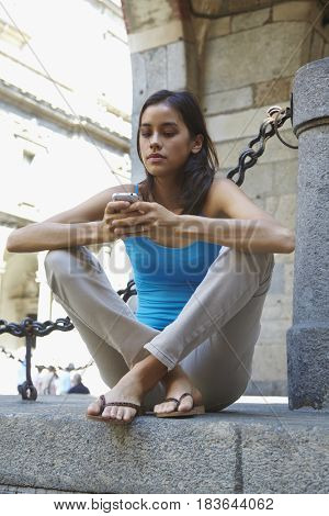 Thai woman text messaging on cell phone