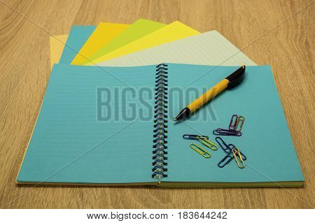 Notebook with colored sheets pen and paper clips