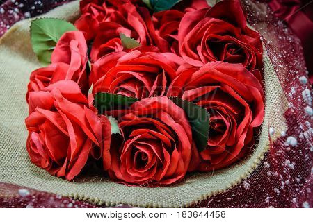 Bouquet of beautiful red roses wrapped into brown sack cloth