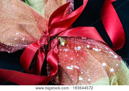 Bouquet flowers with red ribbon wrapped into brown sack cloth