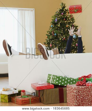 Mixed race boy laying on couch with Christmas gifts