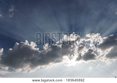 Straight sunrays above dark clouds and bright sky