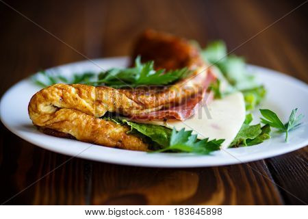 Hot stuffed omelette with cheese, sausage and lettuce leaves on a wooden table