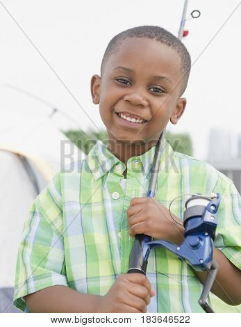 Black boy standing with fishing pole