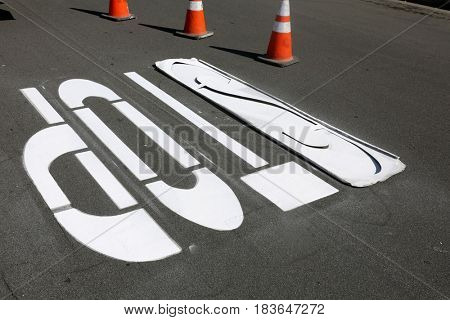 unidentifiable department of transportation workers paint stop signs and cross walks on city streets