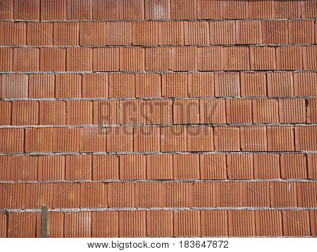 New brick wall built of red bricks on a mortar. Background for construction work. Burnished ground ceramic brickwork, reinforced masonry.