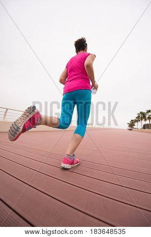 active young beautiful woman busy running on the promenade along the ocean side to keep up her fitness levels as much as possible