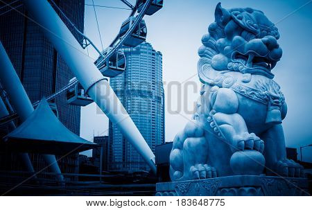 Lion statue in front of modern building in Shanghai financial distric.