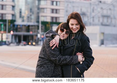 Outdoor portrait of two stylishly dressed beautiful girls and very happy. Girlfriends walk around the city and embrace