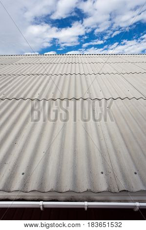 Asbestos slate roof against blue sky close up