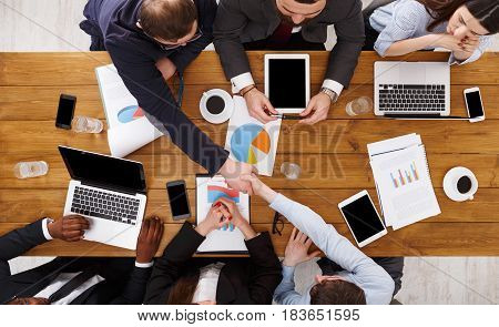Business handshake. Agreement at meeting. Busy people work in office, top view of wooden table