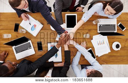 Multiethnic Team put hands together, connection, teambuilding and alliance concept. People in the office, young businessmen and women unite hands for teamwork and cooperation. Top view, overhead