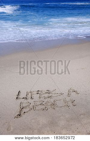 Words Lifes a Beach written in sand with the ocean waves and tide