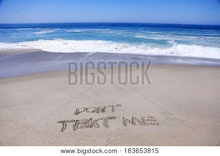 words Don't Text Me written in sand on the beach with the Ocean Tide and Ocean Waves