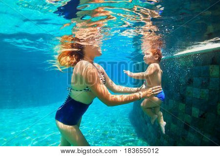 Happy family - mother, baby daughter learn to swim. Girl dive in swimming pool with fun - jump underwater with splashes. Lifestyle, summer children water sports activity, swimming lessons with parent.