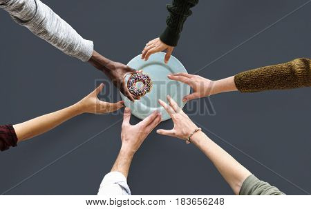 Group of Hands reaching for a donut
