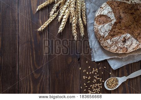 Whole-wheat bread and wheat ears on a wooden table.