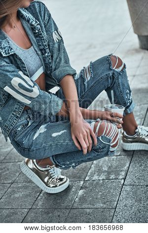 Young and beautiful. Close-up of young woman in jeans wear in casual wear holding a disposable cup while crouching outdoors