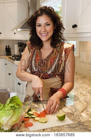 Pregnant Hispanic woman slicing vegetables for salad