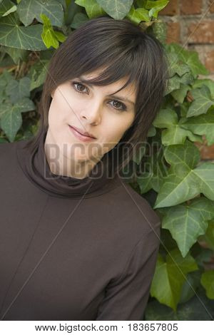 Hispanic woman leaning on ivy-covered wall