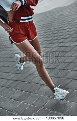 Making an effort to achieve her goal. Close-up of young woman in sport clothing running outdoors