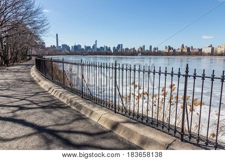 New York City - Panoramic view of modern buildings of Manhattan from Central Park with Jacqueline Kennedy Onassis Reservoir.