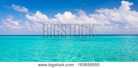 A trip to the summer. The water of the lagoon is turquoise. Light white clouds in the blue summer sky. Maldives. Indian Ocean.