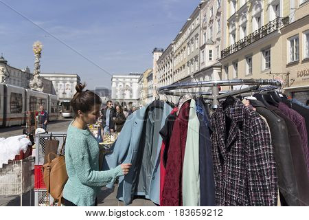 LINZ, AUSTRIA - MARCH 25, 2017:  Young girl looking for second hand clothes in the Hauptplatz Fleamarket in Linz, Austria