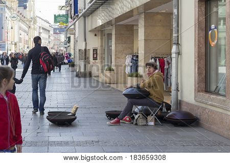 LINZ, AUSTRIA - MARCH 25, 2017:  Street musician playing hang drum while a young girl look at him in the main street of Linz, Austria