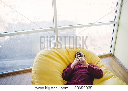 Hipster bag resting in a chair. The young man is and uses smartphone.