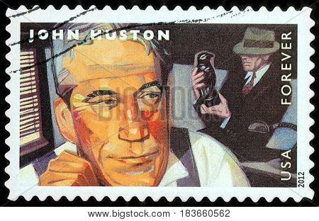 LUGA RUSSIA - APRIL 26 2017: A stamp printed by USA shows famous American film director John Marcellus Huston and actor Humphrey Bogart starring in the film The Maltese Falcon circa 2012