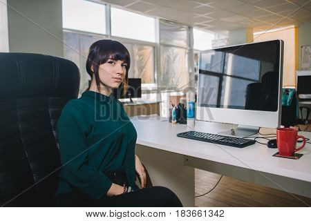 Young beautiful business woman in a dark jacket sitting at workplace near the computer in the office chair. The modern office worker. Modern office