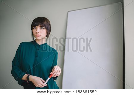 office business people and education concept - close up of woman with marker writing or drawing something on flip chart