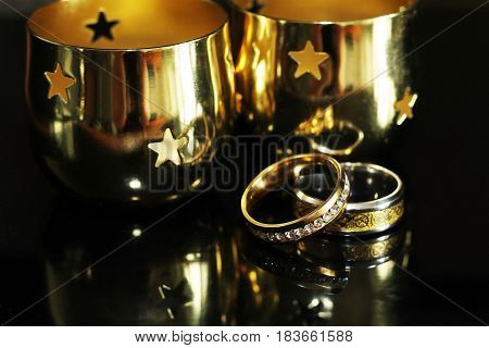 Candlestick And Wedding Rings On A Black Background
