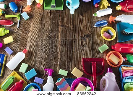 Spring cleanup theme. Variety of colorful house cleaning products on a rustic wooden table. Top view.