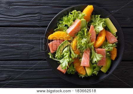 Salad Of Salmon, Oranges, Avocado And Frisee Close-up On A Plate. Horizontal Top View