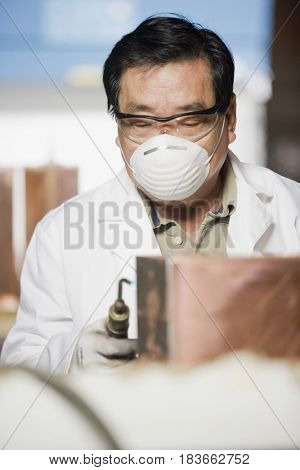 Asian factory worker wearing protective mask and goggles