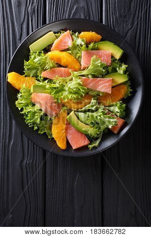 Salad Of Salmon, Oranges, Avocado And Frisee Close-up On A Plate. Vertical Top View